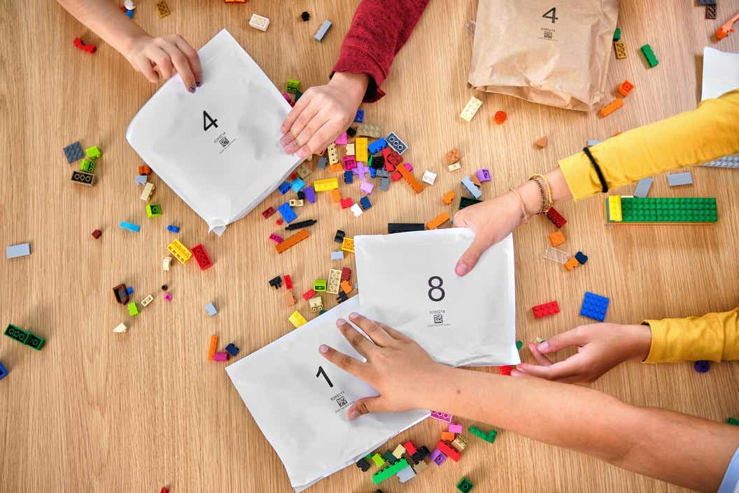 Image of children's hands holding paper bags and LEGO bricks