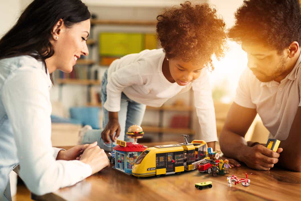 Two adults and a child playing with the LEGO CITY set on a table