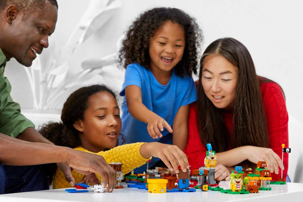 Image of adults and children playing with LEGO Super Mario together
