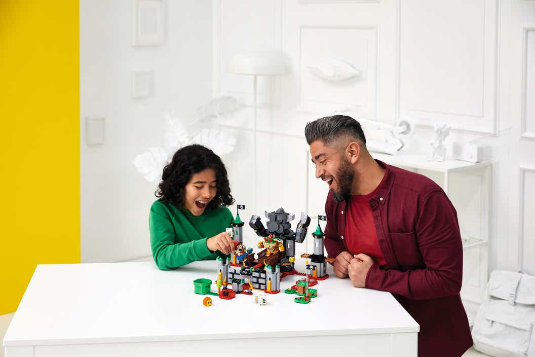 Man and child sitting together and playing with a LEGO Super Mario set