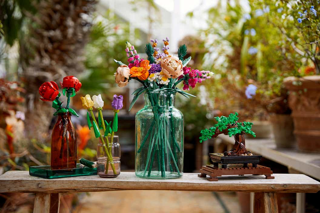 Lifestyle image of three LEGO flower bouquets in vases next to a LEGO Bonsai Tree in a botanical setting