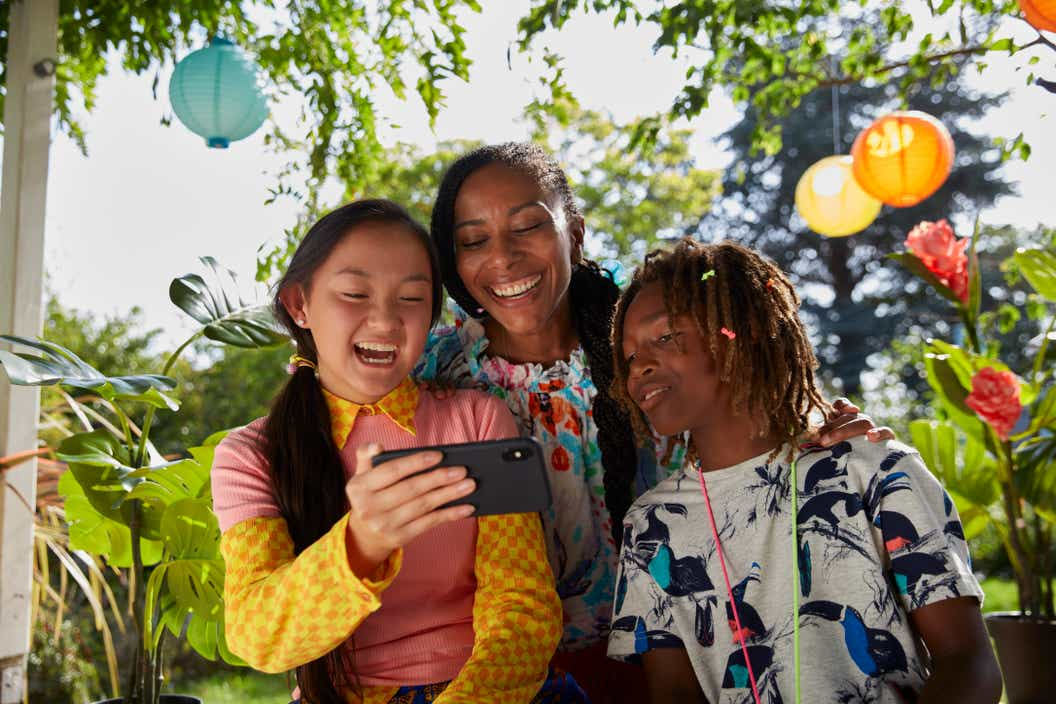 Lifestyle image of three children looking at the LEGO VIDIYO app on a cell phone