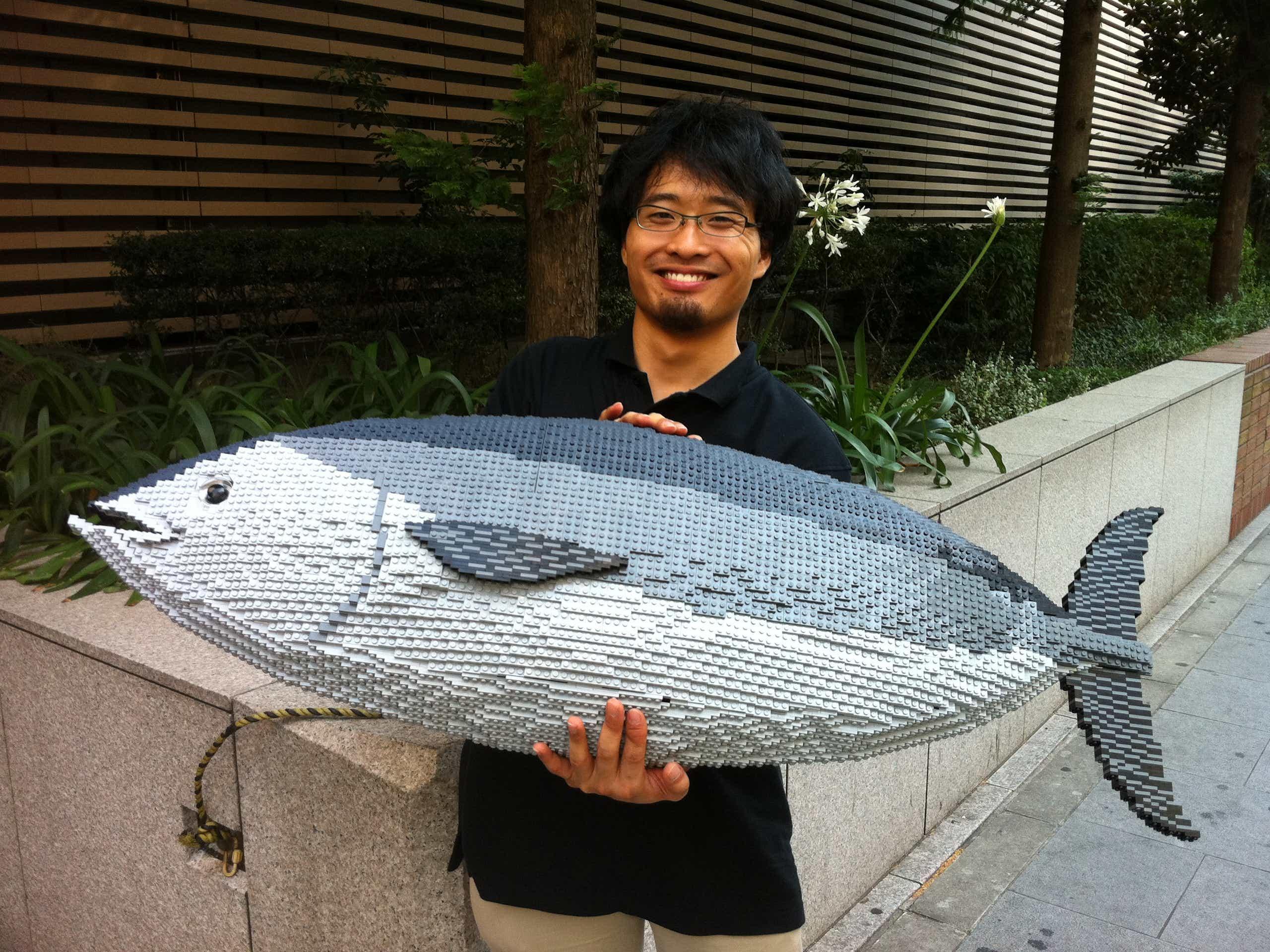 Uomo in posa con un modello LEGO di un grande pesce