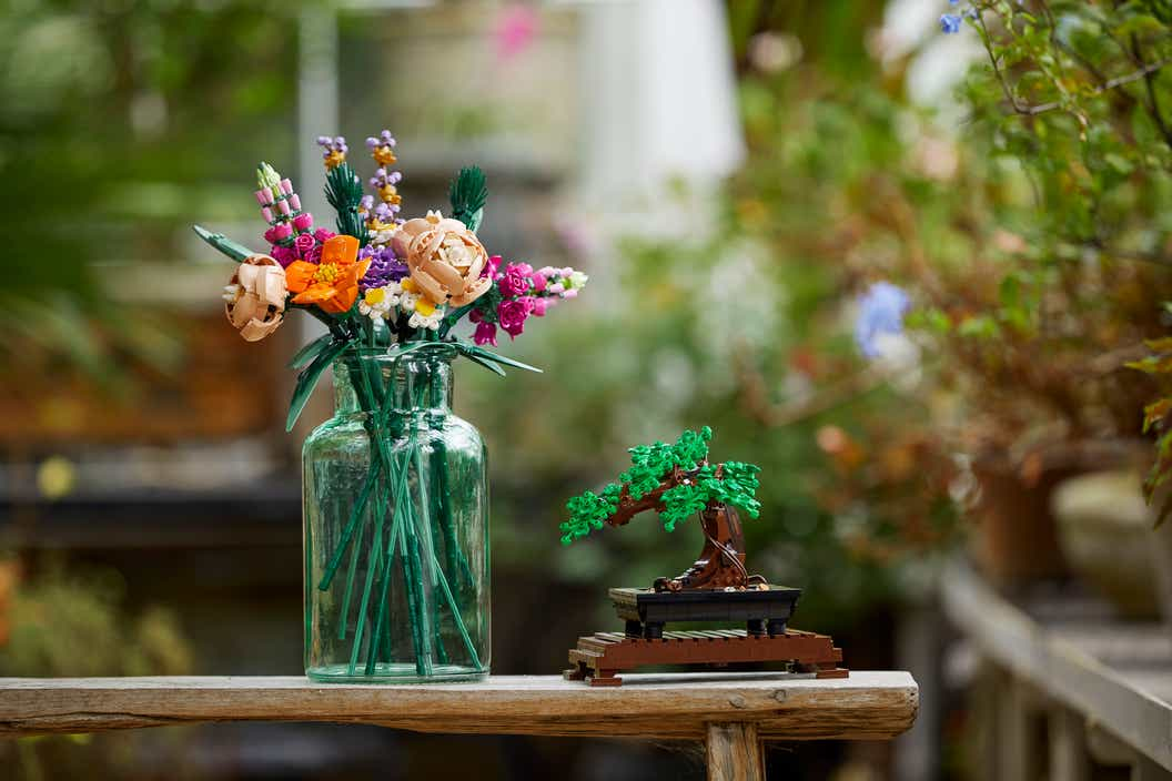 Lifestyle image of a LEGO flower bouquet in a vase next to the LEGO Bonsai Tree in a botanical setting.