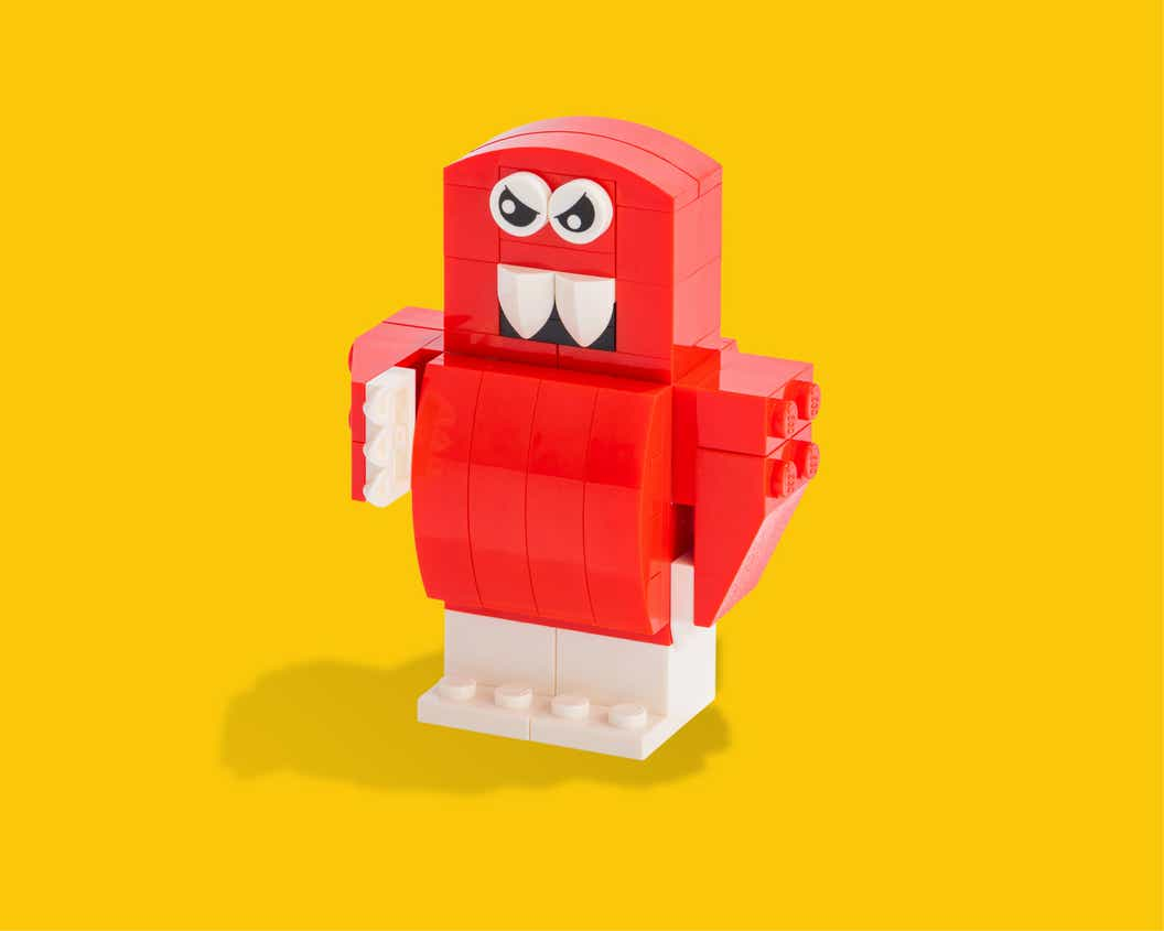 Image of a red LEGO figure with angry experession and fangs