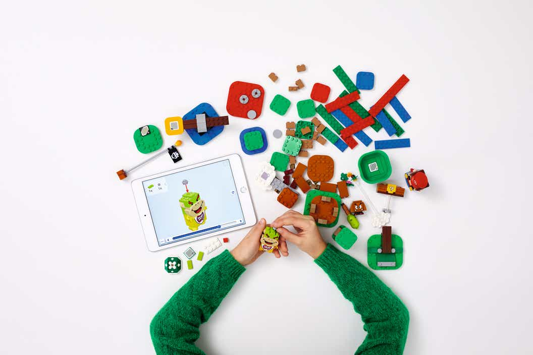 Child using a tablet displying digital building instructions in order to construct with LEGO bricks