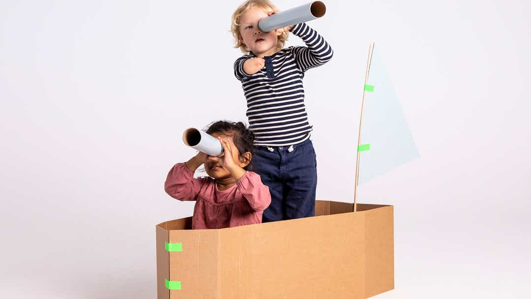Image of girl and boy playing in a large cardboard box shaped as a boat