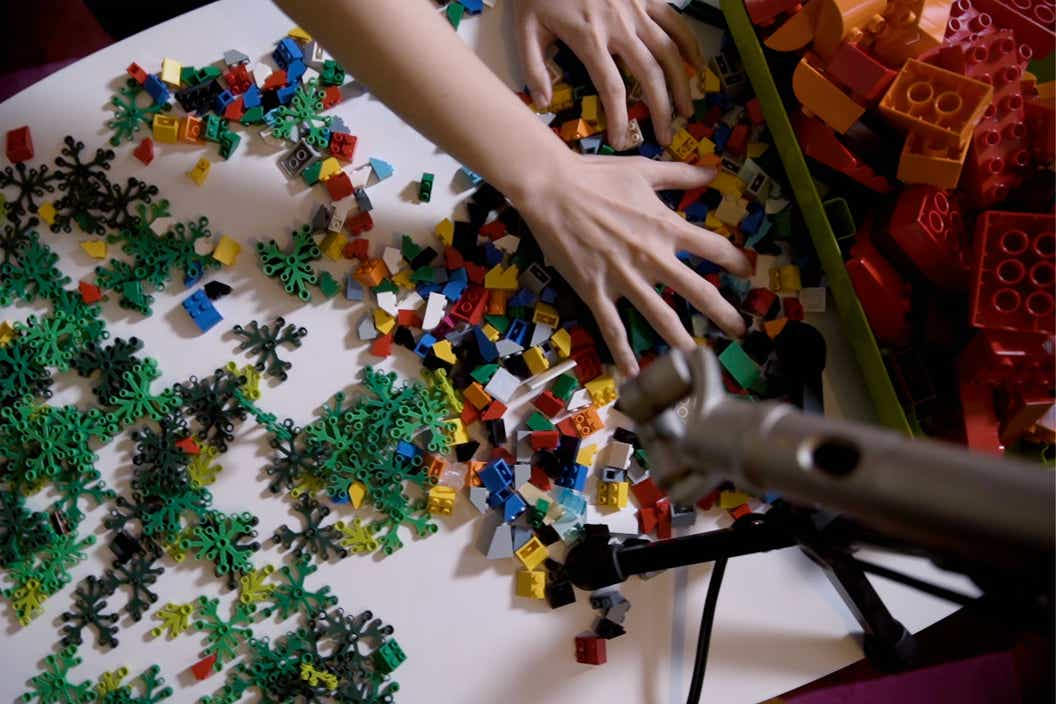 Lifestyle image of LEGO pieces spred across a table and a hand looking for bricks to start building