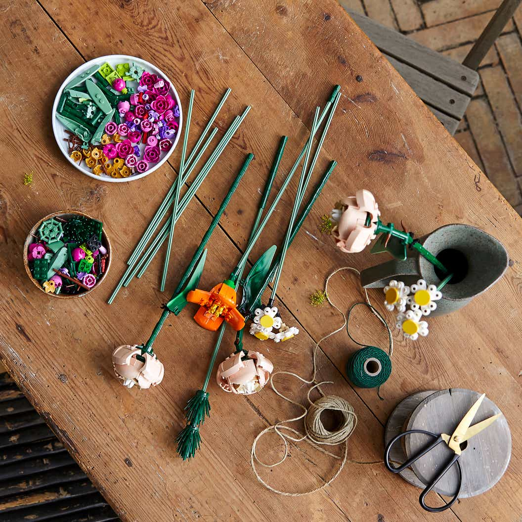 Lifestyle image of LEGO flower stems, snapdragons, roses, poppies, asters, daisies, and different grasses from the LEGO flower bouquet set