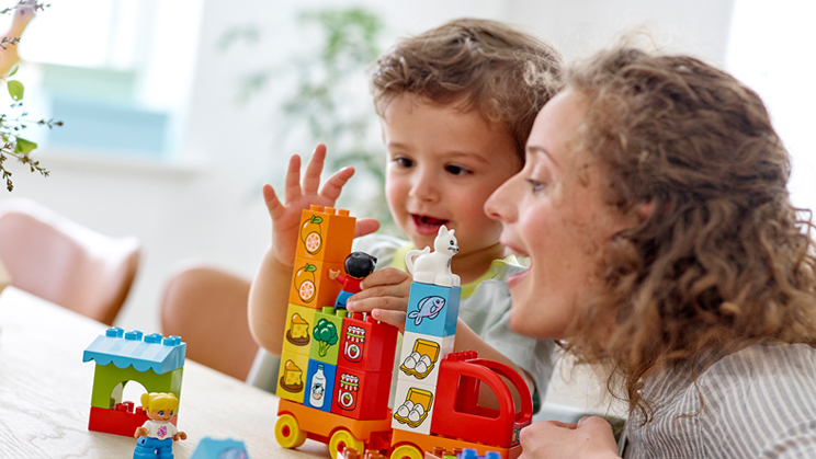 Elternteil und Kind spielen mit DUPLOSteinen