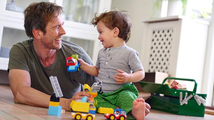 Elternteil spielt mit Kind und DUPLO Fahrzeugen
