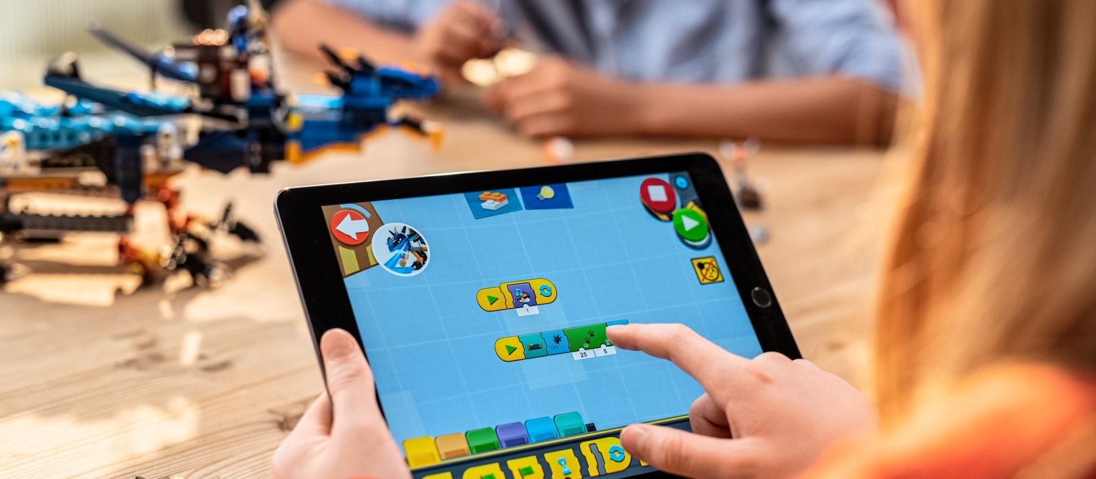 Kids coding with the LEGO® BOOST app to make the NINJAGO® Stormbringer move